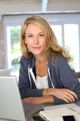 Middle aged blond woman working at home with laptop
